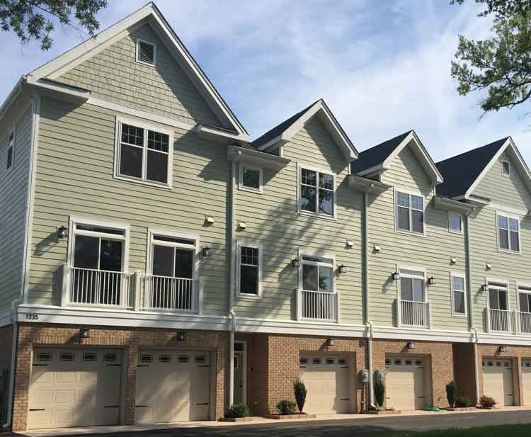 Multi-Family Construction & Renovation featuring townhouses with green siding and brick garages underneath by Covington Contracting