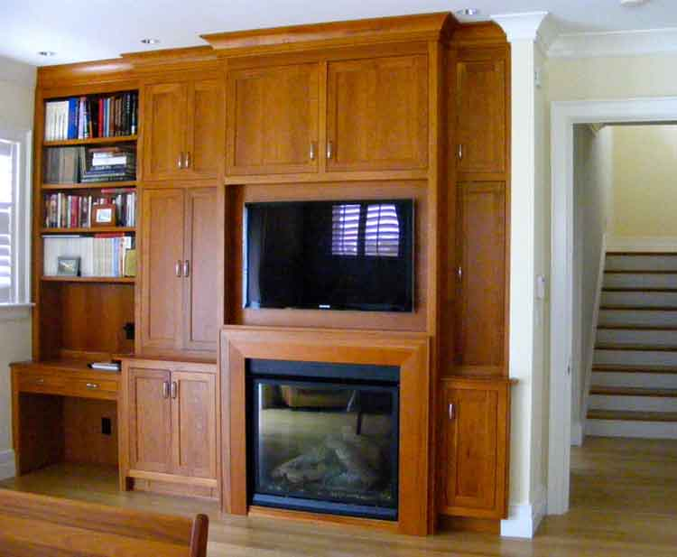 Wood built-in cabinets with a TV and fireplace in a home in Virginia Beach built by Covington Contracting