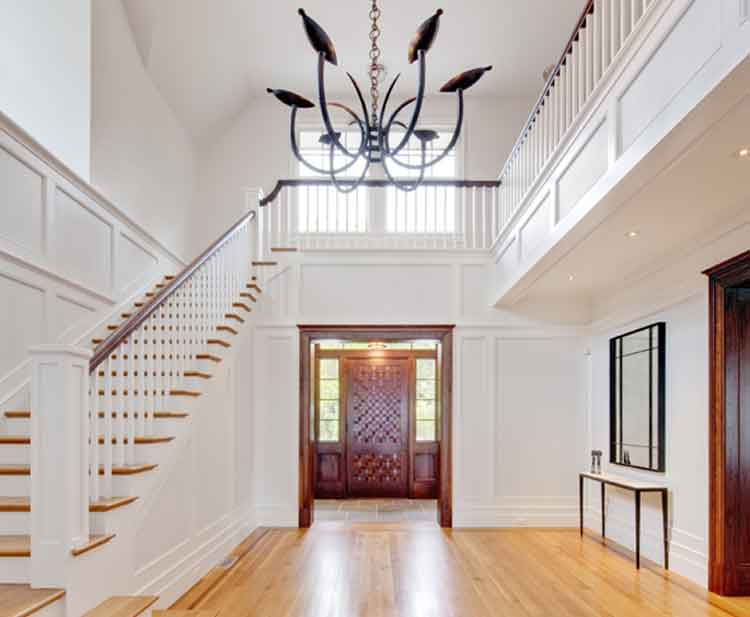 Foyer with dark entry door and sweeping staircase in a custom home in Virginia Beach built by Covington Contracting