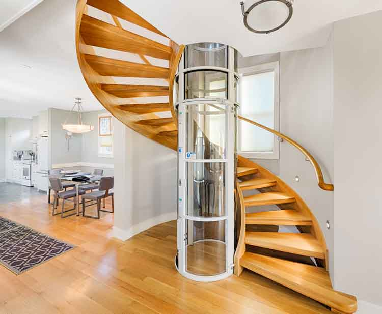 Spiral wooden staircase with tubular elevator in a custom home in Norfolk Virginia built by Covington Contracting