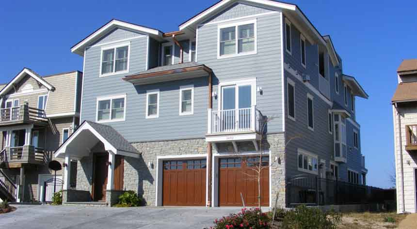 Blue front exterior with wood garage doors of a custom home in Virginia Beach built by Covington Contracting