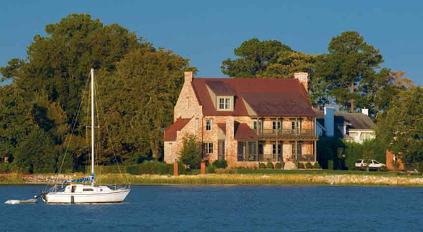 Gorgeous view of a home from the water with a sailboat anchored in Norfolk Virginia by Covington Contracting