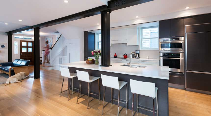 A modern kitchen renovation with an open concept with a woman coming down the stairs in Norfolk Virginia