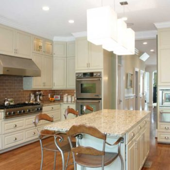 A Modern Kitchen With White Cabinets And Counter Tops With Stainless Steel Appliances