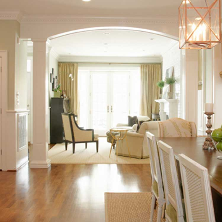 A View Through Columns From A Dining Room Into A Living Room With Hardwood Floors And A Large Window