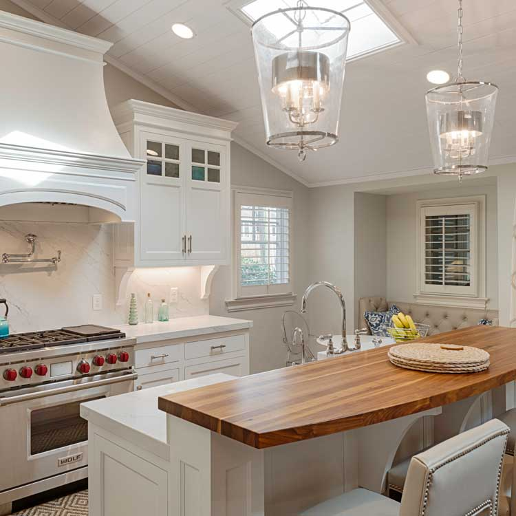 A New Kitchen With White Cabinets, Stone And Wood Counters And Stainless Steel Appliances