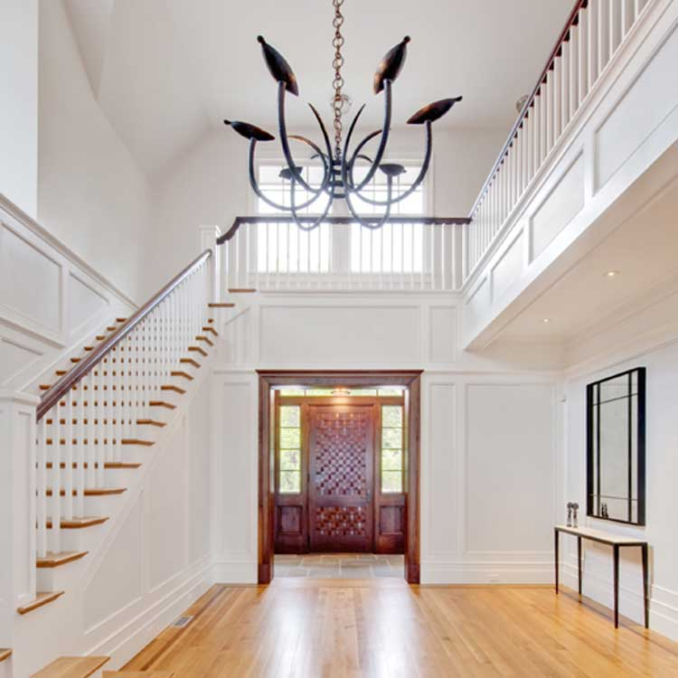 A Beautiful Home Entrance With A Dark Wood Door And Grand Staircase