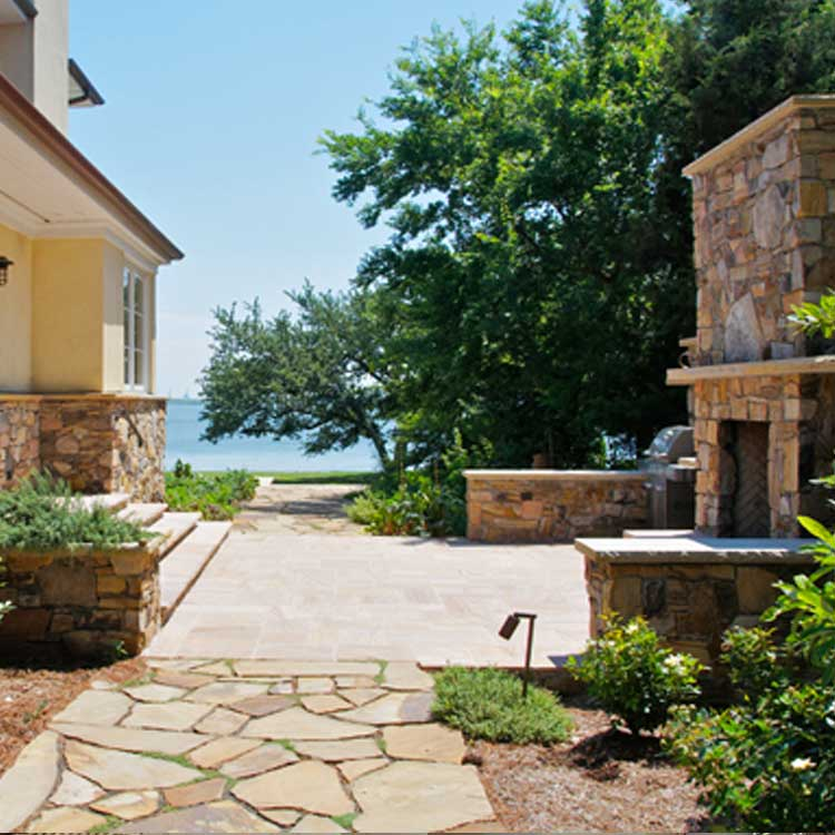 A Beautiful Outdoor Space With A Stone Patio And Fireplace