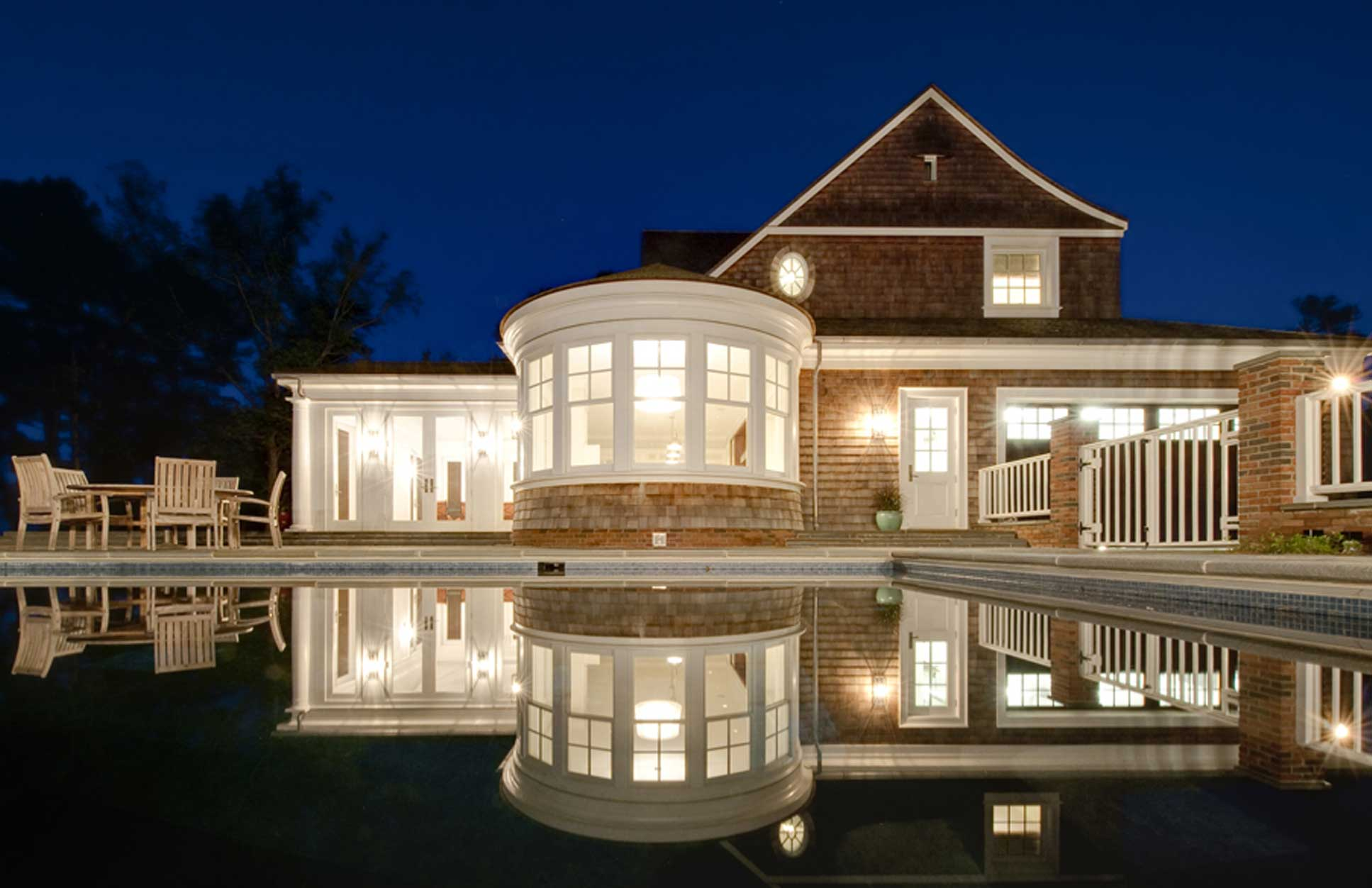 A backyard at night with lights reflecting on the pool in Little Neck built by Covington Contracting luxury custom homebuilder in Hampton Roads Virginia
